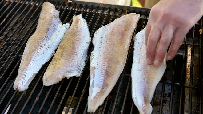 Chef Daniel Dean places walleye fillets to cook on the grill for walleye tacos at the Nick's Third Floor booth July 9 at Summertime by George! in St. Cloud.