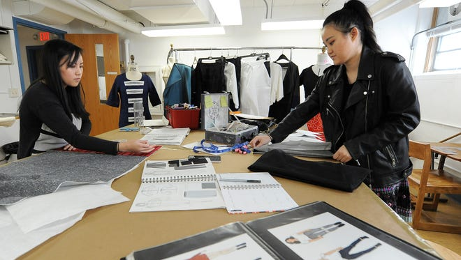 Panyia Xiong (left) and Beth Yang preparing for Mount Mary's Creo fashion show in May. Both incorporate traditional Hmong garment styles to create modern looks.