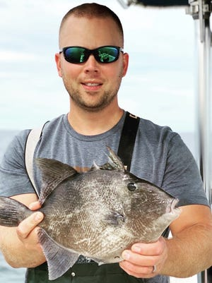 Capt. Matt Blazis holds a rare tropical gray triggerfish that was caught in one of his lobster pots in Cape Cod Bay.