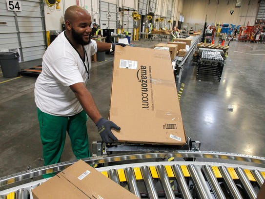 Leacroft Green places a package on a conveyor at an Amazon.com fulfillment center in Goodyear, Ariz., in 2010.