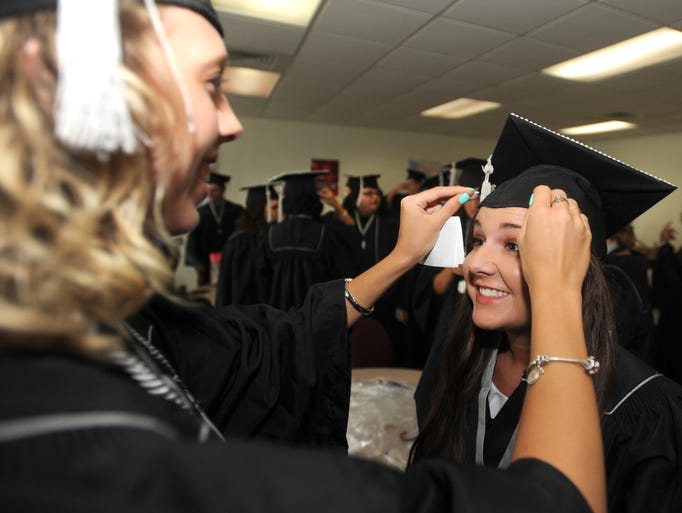 Lacey Buchannan, 17, left, helps  Lisa Dowdy, 18, with  her cap  during ceremonies for the Buncombe County Middle College at Asheville- Buncombe Technical Community College Wednesday. Thirty students graduated. John Coutlakis 6-11-14