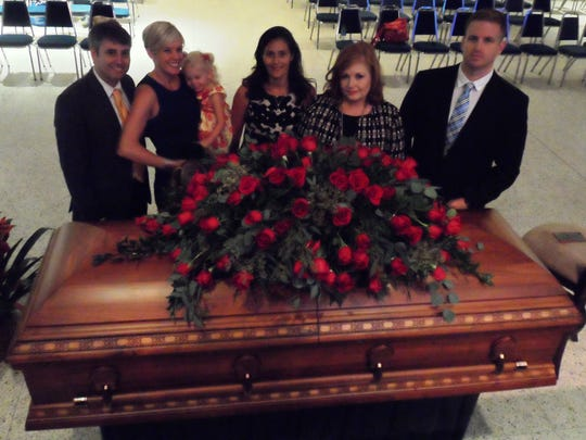 Members of the family of the late Alexandria Mayor Ned Randolph stand near his casket in Convention Hall on Thursday. From left are Randolph's son, Edward G. Randolph III and his wife, Jessica Shank Randolph, who is holding their 2-year-old daughter, Polly Jane Randolph; Randolph's daughter, Aimee Randolph Lapic; Randolph's widow, Deborah Broussard Randolph; and Randolph's stepson, Matthew A. Dunn.