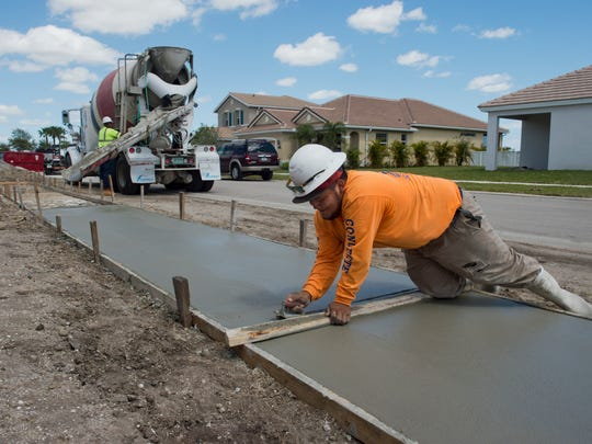 Joel Andrade of Jesus Gamez Concrete & Masonry in Palm Bay, puts down new sidewalks in the Victoria Parc development on March 20, 2017, in Port St. Lucie.