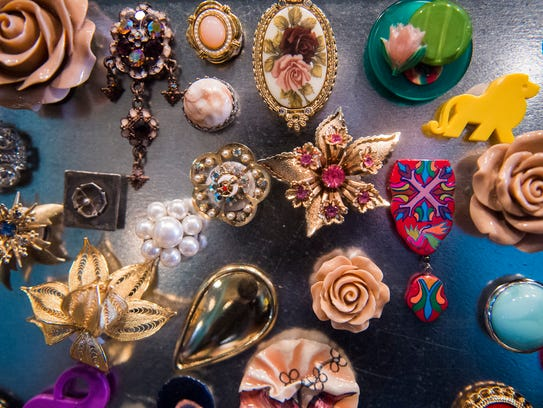 Upcycled brooches are displayed in a booth belonging