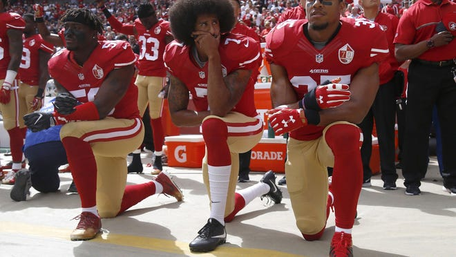 From left, The San Francisco 49ers' Eli Harold (58), Colin Kaepernick (7) and Eric Reid (35) kneel during the national anthem before a game against the Dallas Cowboys on October 2, 2016, at Levi's Stadium in Santa Clara, Calif.