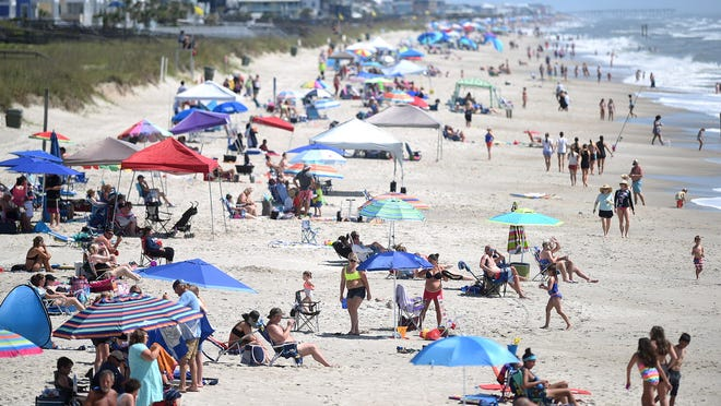People crowd the beach just north of Kure Beach Pier in Kure Beach in May 23. Despite COVID-19 and Hurricane Isaias, the short-term rental market has fared well in recent months.