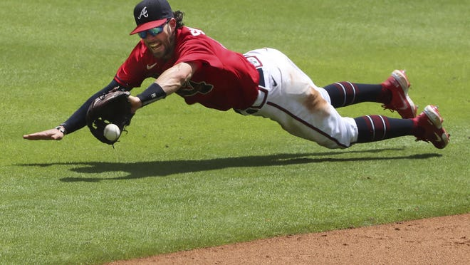 Braves shortstop Dansby Swanson makes a diving catch and holds New York Mets base runner J.D. Davis at third base on a ball hit by Amed Rosario during the sixth inning on Sunday in Atlanta. The Braves are scheduled to play the Toronto Blue Jays on Tuesday night.