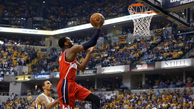 Washington's John Wall lays the ball in against Indiana's George Hill at Bankers Life Fieldhouse on Tuesday.