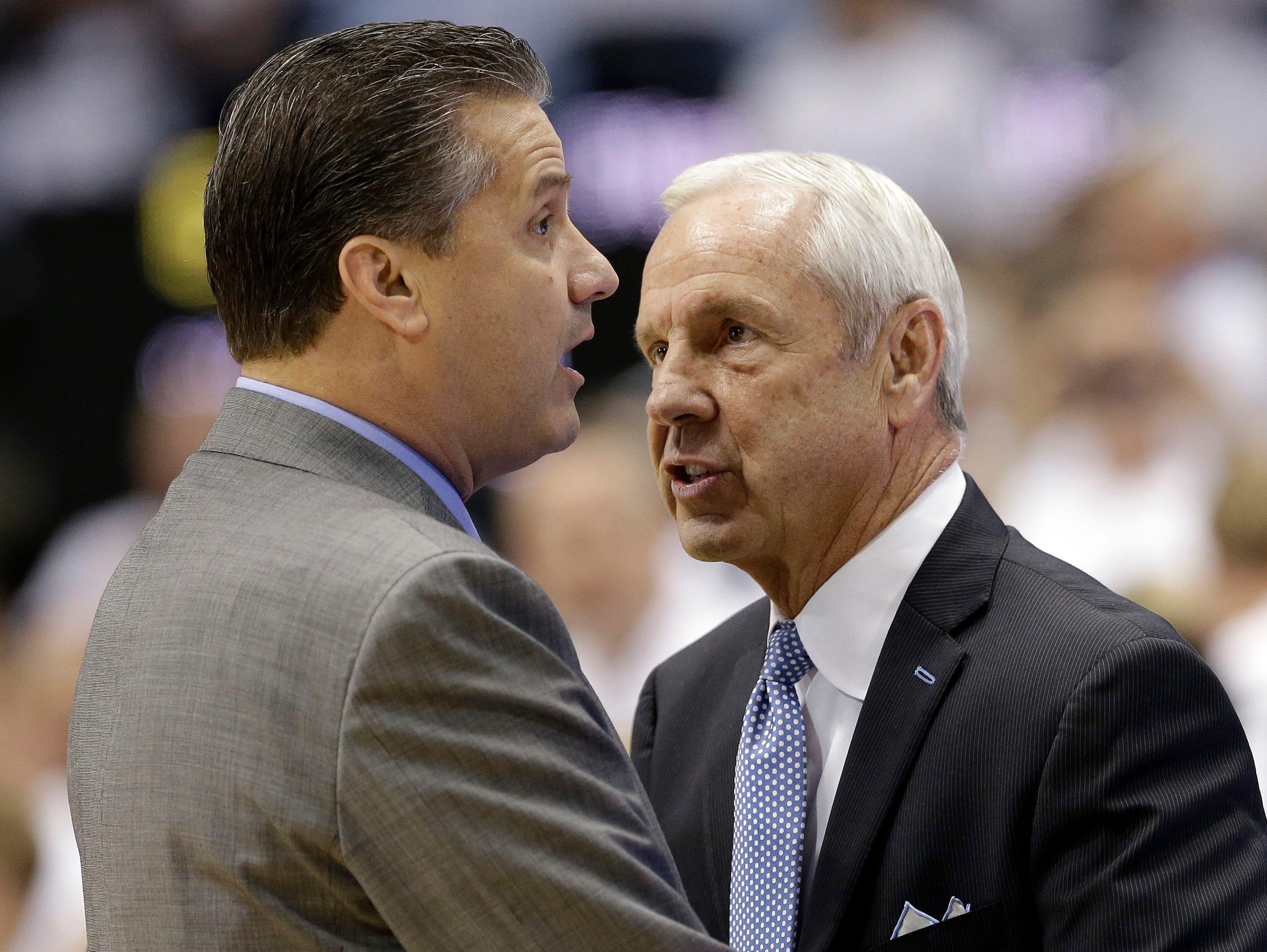 Kentucky coach John Calipari, left, and North Carolina coach Roy Williams speak before an NCAA college basketball game in Chapel Hill, N.C., Saturday, Dec. 14, 2013. (AP Photo/Gerry Broome)