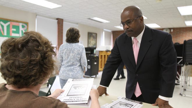 James Sheppard votes at Christ the Good Shepherd Lutheran Church. Jeanne Turner, election inspector, hands him his primary ballot.