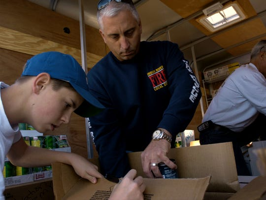 Indian River County Fire Rescue Lt. David Dangerfield works with Cole Daniels, 13, of Sebastian, to put together a Thanksgiving meal for the needy in November 2005. Dangerfield, suffering from post-traumatic stress disorder, committed suicide in October 2016. In March 2018, the Florida Legislature passed a bill requiring that first responders get PTSD coverage under workers' compensation.