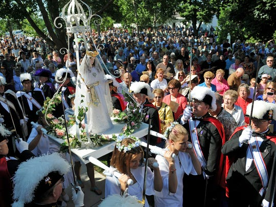 A statue of Mary is carried in for the beginning of the mass and rosary procession for the Feast of the Assumption of the Blessed Virgin Mary at the National Shrine of Our Lady of Good Help chapel in Champion.