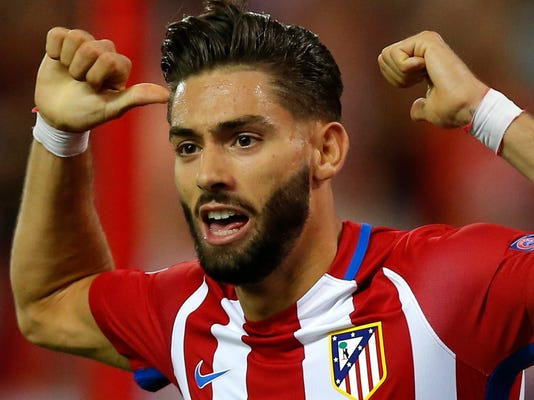 FILE - In this Wednesday, Sept. 28, 2016 file photo, Atletico's Yannick Carrasco celebrates scoring the opening goal during the Champions League group D soccer match between Atletico Madrid and FC Bayern Munich at the Vicente Calderon stadium in Madrid, Spain. Atletico Madrid says it has reached a deal for the transfer of midfielder Yannick Carrasco and Nicolas Gaitan to Chinese club Dalian Yifang. (AP Photo/Daniel Ochoa de Olza, File)