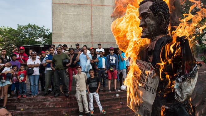 "A sign on a President Obama dummy reading, ""Obama abolish the decree now, "" is burned as the ""Burning of Judas,"" during an Easter celebration at El Valle shantytown in Caracas on April 5."