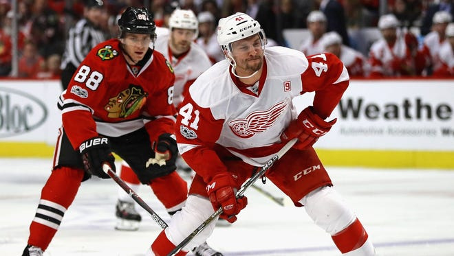 Red Wings forward Luke Glendening readies to shoot in front of the Blackhawks' Patrick Kane Tuesday in Chicago.