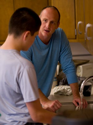North Posey High School teacher Nicholas Berry and his pupil, Alex Bare, 13, have a few minutes to talk as they wash the dishes after class recently.