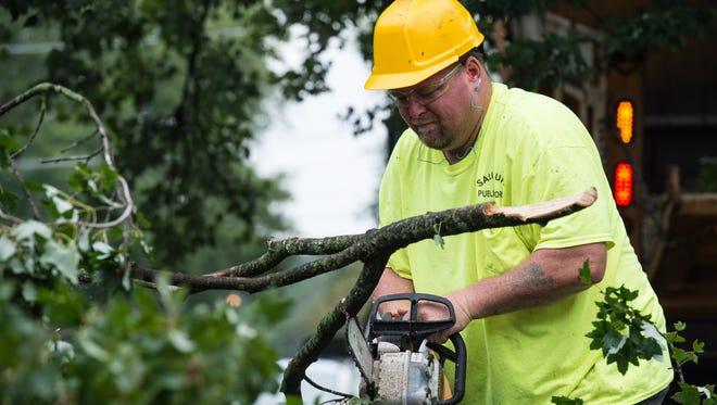 A worker uses a chainsaw cut tree branches that have fallen onto the street.