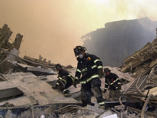 New York City firefighters maneuver around the debris
