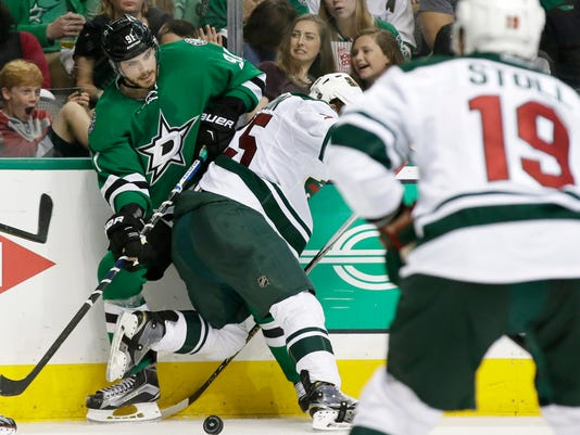 Dallas Stars center Tyler Seguin (91) tangles with Minnesota Wild defenseman Jonas Brodin (25) for the control of the puck during the third period in Game 2 in the first round of the NHL Stanley Cup playoffs Saturday, April 16, 2016, in Dallas. (AP Photo/LM Otero)