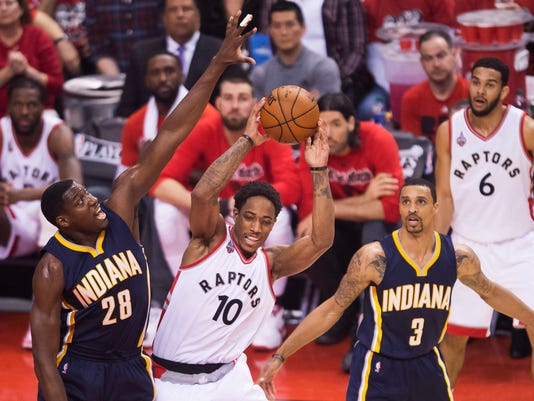 Toronto Raptors guard DeMar DeRozan (10) moves the ball past Indiana Pacers centre Ian Mahinmi (28) and Pacers guard George Hill (3) during Game 7 of round one NBA playoff basketball action in Toronto on Sunday, May 1, 2016. (Nathan Denette/The Canadian Press via AP)