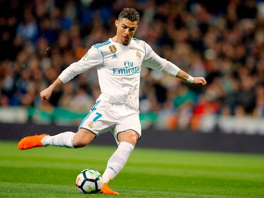 FILE - In this file photo dated Sunday, March 18, 2018, Real Madrid's Cristiano Ronaldo takes a free kick during a Spanish La Liga soccer match against Girona at the Santiago Bernabeu stadium in Madrid, Spain.  Ronaldo will be rested along with other key players for Real Madrid's match at Las Palmas on upcoming Saturday March 31, 2018. (AP Photo/Paul White, FILE)