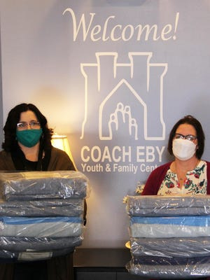 Rachel Everett and Melissa Austin of Coach Eby Youth and Family Center in Coldwater hold blankets provided by American Red Cross, for use when the warming center opens.