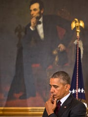 President Barack Obama pauses in front of a painting