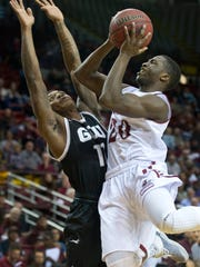 New Mexico State's Sidy Ndir drives to the basket against Grand Canyon's De'Andre Davis during first half action Thursday night at the Pan American Center.