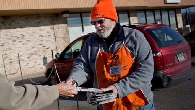 Volunteer Tom Gillette, of Port Huron, takes a donation while hawking newspapers to raise money for Old Newsboys Friday, Dec. 4, 2015 at Country Style Marketplace in Fort Gratiot.
