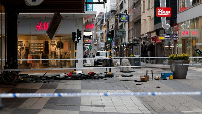 "A street is cordoned off following Friday's attack in central Stockholm, Sweden. A Swedish prosecutor says a person has been formally identified as a suspect ""of terrorist offenses by murder"" by driving a hijacked truck into a crowd of pedestrians."