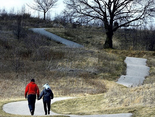 Walkers take advantage of the paths at the former Hawk Lake golf course in West Manchester Township earlier this year. Soon people will have to blaze new trails as Memorial Hospital plans to close the current paths during construction of its new facility on the site.
