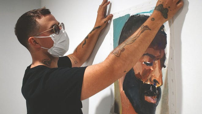 FR MoCA co-founder  Harry Gould Harvey, IV hangs a painting by Shuriya Davis.