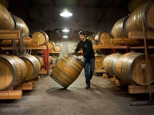Rich Swanger, assistant winemaker at St. Innocent Winery, moves a barrel to be cleaned.