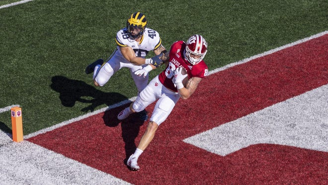 Indiana tight end Peyton Hendershot (86) crosses into the end zone to score ahead of Michigan linebacker Ben VanSumeren (40) during the first half of an NCAA college football game Saturday, Nov. 7, 2020, in Bloomington, Ind.