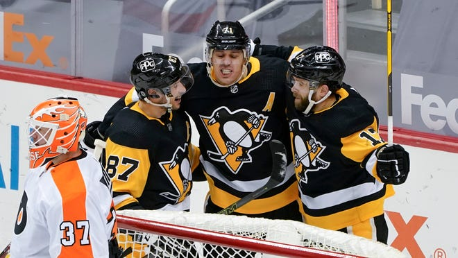 Pittsburgh Penguins' Evgeni Malkin, center, celebrates with Sidney Crosby (87), and Bryan Rust (17) after scoring on Philadelphia Flyers goaltender Brian Elliott (37) during the first period of an NHL hockey game, Saturday, March 6, 2021, in Pittsburgh. (AP Photo/Keith Srakocic)