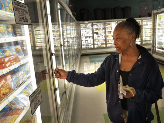 "Joyce Robertson of Wilmington shops for food at the Fresh Grocer in the Adams Four Shopping Center. ""Whatever they got on sale, I try to get it,"" Robertson said."