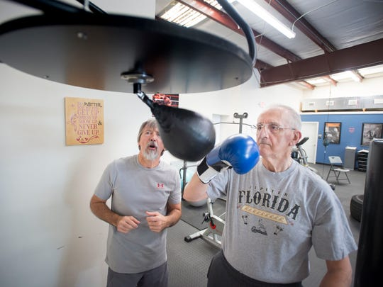 Coach Shawn Callaghan, left, instructs boxer Ken Doering as he works the punching bag during the Parkinson's boxing class at Rock Steady Boxing Emerald Coast in Gulf Breeze on Friday, January 12, 2018.