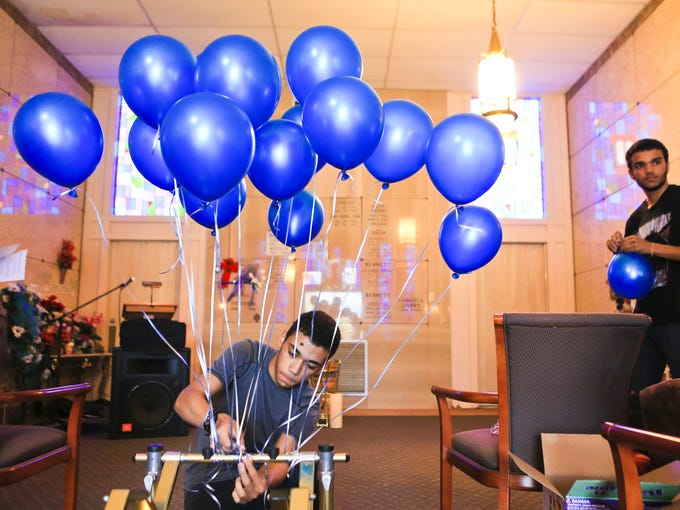 Austin Collins, 17, ties a balloon to a casket stand