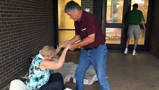 TCPalm reporter Elliot Jones helps a woman at a hurricane shelter that opened for Hurricane Matthew in 2016.