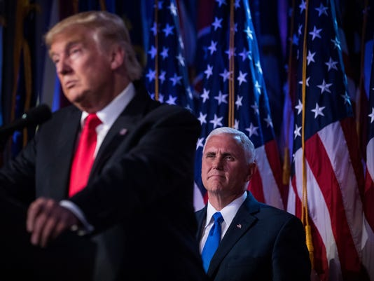 Donald Trump speaks as his running-mate, Mike Pence, looks on at his election night party early Wednesday morning in New York.