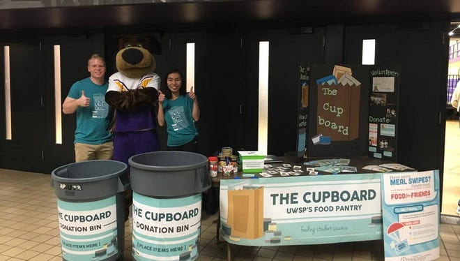 Volunteers for The Cupboard pose in front of their table in the Dreyfus University Center at the University of Wisconsin-Stevens Point.