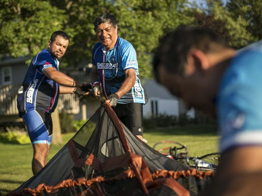 Marco Prada, center, and his sons Marco Prada, right, foreground, of Iowa City and Daniel Prada, back left, of Las Vegas with cycling team Dublin Underground in Fort Dodge Monday July 20, 2015, during RAGBRAI XLIII.