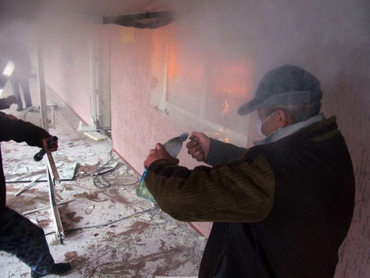 pro-Russia protester lights a Molotov cocktail during the storming ...
