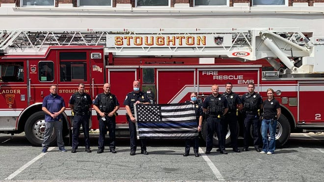 Members of the Stoughton Police Department, including Deputy Chief Brian Holmes, center-left, and Police Chief Donna McNamara, center-right, pose with the thin blue line flag touring Massachusetts after it was removed from a Hingham fire truck in July. The photo was taken in front of a Stoughton Fire Department ladder truck at the Freeman Street fire station, Tuesday, Aug. 25, 2020.