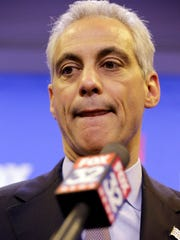 Chicago Mayor Rahm Emanuel listens to a reporter's