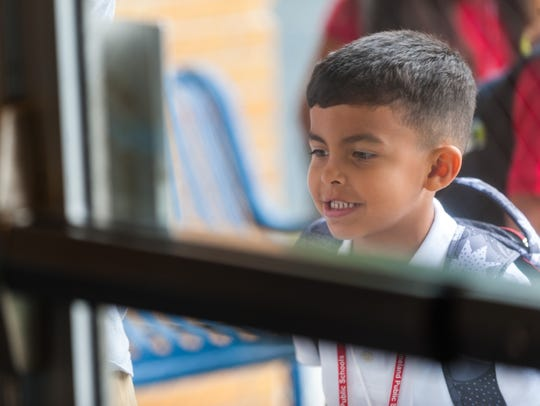 Kindergartner Eastin Torres looks into the front door