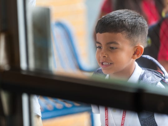 Kindergartner Eastin Torres looks into the front door on his first day of school at Winslow Elementary on Wednesday, September 6.