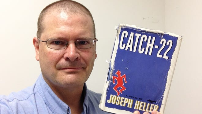 Scott Broden holds his copy of Catch-22 after having read the 443-page novel by Joseph Heller.
