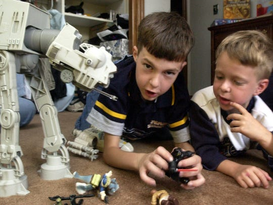 "Brothers Luke Nudson, 9, left, and Matthew Nudson, 5, play with their Star Wars toys in their Visalia home on Friday, May 13, 2005. Ten years later, their love for the series is once again sparked with the release of ""Star Wars: The Force Awakens."""
