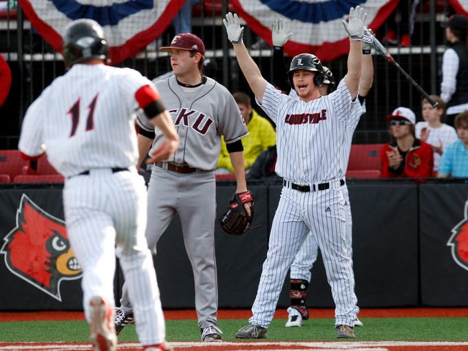 U of L's Danny Rosenbaum, #8, waves in his teammate Zach Lucas, #11, left, as they score two runs for the Cardinals as they played EKU at Patterson Stadium.  EKU's Matt Lynch, #27, looks on. Feb. 19, 2014